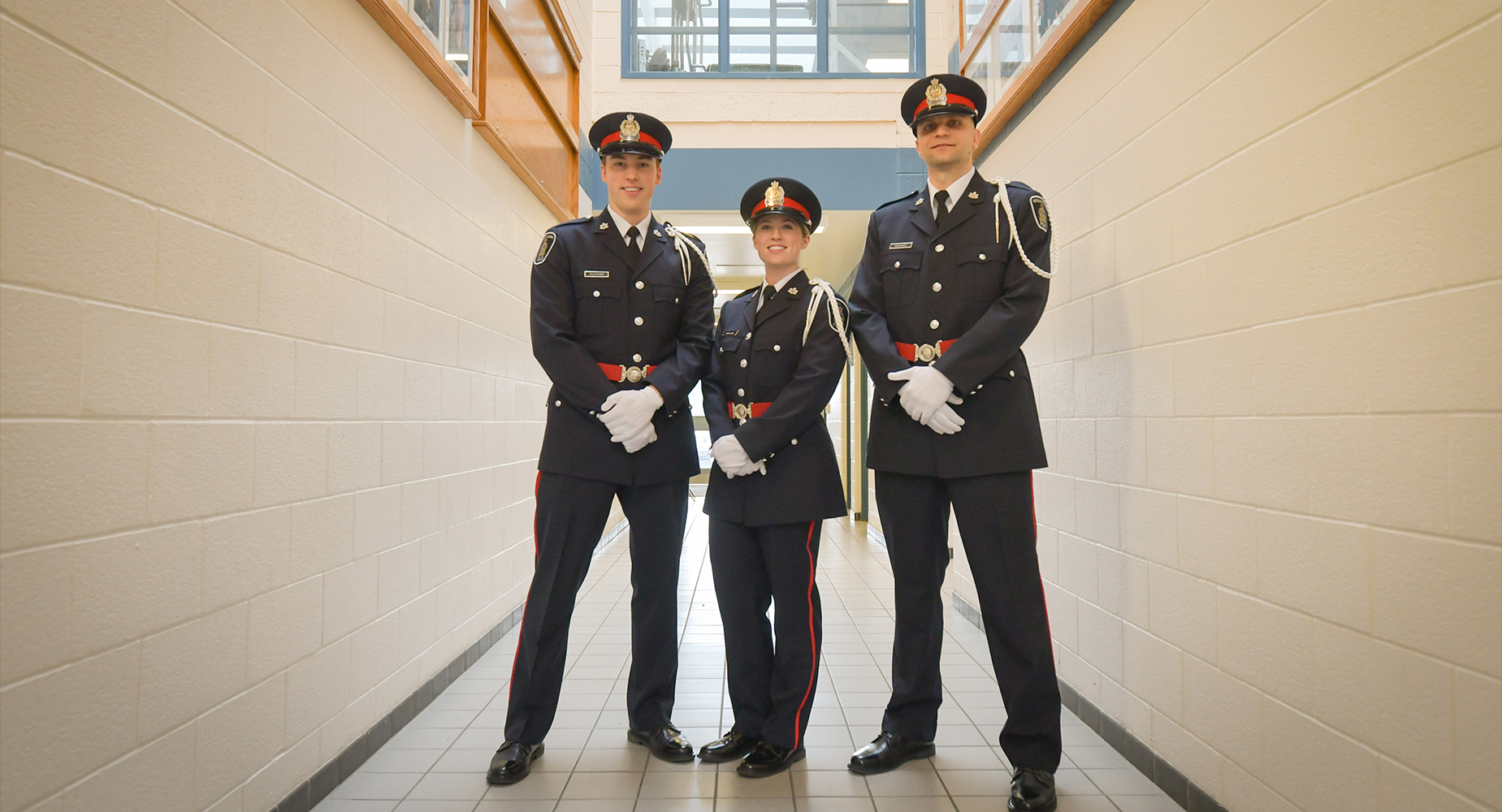 Three new police officers in dress uniform